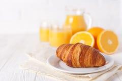 新近地被烘烤的新月形面包,橙汁,新鲜水果,在白色木背景的果酱 法国早餐新鲜的酥皮点心 免版税库存照片