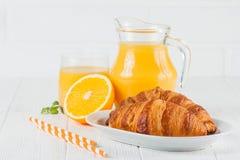 新近地被烘烤的新月形面包,橙汁,新鲜水果,在白色木背景的果酱 法国早餐新鲜的酥皮点心为早晨 图库摄影