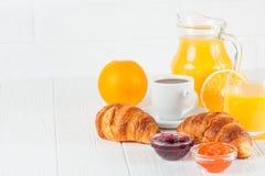 新近地被烘烤的新月形面包,橙汁,新鲜水果,在白色木背景的果酱 法国早餐新鲜的酥皮点心为早晨 库存照片