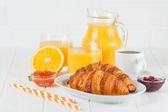 新近地被烘烤的新月形面包,橙汁,新鲜水果,在白色木背景的果酱 法国早餐新鲜的酥皮点心为早晨 免版税库存照片