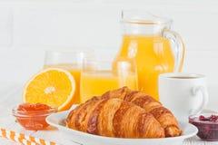 新近地被烘烤的新月形面包,橙汁,新鲜水果,在白色木背景的果酱 法国早餐新鲜的酥皮点心为早晨 免版税图库摄影