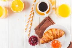 新近地被烘烤的新月形面包,橙汁,新鲜水果,在白色木背景的果酱 法国早餐新鲜的酥皮点心为早晨 免版税库存图片