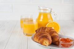 新近地被烘烤的新月形面包,橙汁,新鲜水果,在白色木背景的果酱 法国早餐新鲜的酥皮点心为早晨 库存图片