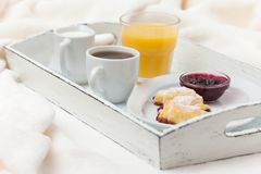 新近地被烘烤的新月形面包,橙汁,果酱,杯子在白色木盘子的无奶咖啡在格子花呢披肩 自创的曲奇饼 新鲜的酥皮点心为 库存照片