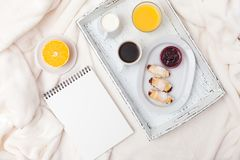 新近地被烘烤的新月形面包,橙汁,果酱,杯子在白色木盘子的无奶咖啡在格子花呢披肩 自创的曲奇饼 新鲜的酥皮点心为 免版税库存照片