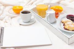 新近地被烘烤的新月形面包,橙汁,果酱,杯子在白色木盘子的无奶咖啡在格子花呢披肩 自创的曲奇饼 新鲜的酥皮点心为 免版税库存图片