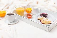 新近地被烘烤的新月形面包,橙汁,果酱,杯子在白色木盘子的无奶咖啡在格子花呢披肩 自创的曲奇饼 新鲜的酥皮点心为 库存图片
