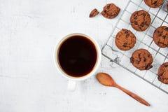 新近地被烘烤的曲奇饼和咖啡杯在白色木表上 免版税库存图片