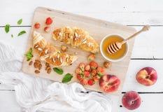 新近地被烘烤的杏仁新月形面包用庭院草莓 免版税图库摄影