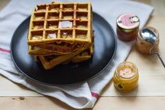 新近地被烘烤的甜可口开胃比利时华夫饼干用在一个黑色的盘子的蜂蜜在一张木桌上 库存图片