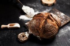 新近地被烘烤的面包、面粉和蕃茄在一个木板在桌上 免版税图库摄影