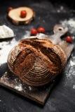 新近地被烘烤的面包、面粉和蕃茄在一个木板在桌上 免版税库存照片