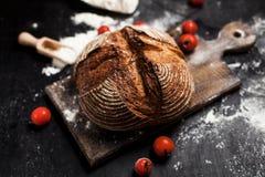 新近地被烘烤的面包、面粉和蕃茄在一个木板在桌上 免版税库存图片