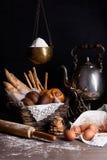 新近地被烘烤的面包的分类和酥皮点心、鸡蛋、面粉和茶壶,在土气木桌上 免版税库存照片
