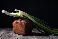 新近地被烘烤的黑面包大面包和新鲜的春天葱说谎 免版税图库摄影