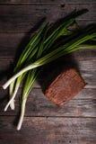 新近地被烘烤的黑面包大面包和新鲜的春天葱说谎 库存图片