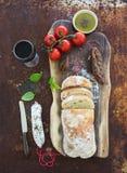 新近地被烘烤的ciabatta面包用樱桃蕃茄,蒜味咸腊肠、pesto调味汁、蓬蒿和杯在核桃木头的红葡萄酒上 免版税库存图片