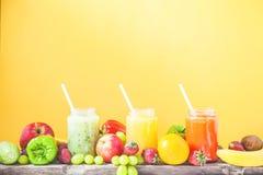 新近地被紧压的果汁,在一黄色backg的圆滑的人橙黄青绿的香蕉柠檬苹果橙色猕猴桃葡萄草莓 库存照片
