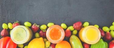 新近地被紧压的果汁,在一黑暗的backgro的圆滑的人橙黄青绿的香蕉柠檬苹果橙色猕猴桃葡萄草莓 免版税库存照片