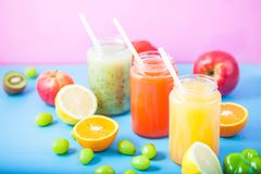 新近地被紧压的果汁,在明亮的蓝色的圆滑的人橙黄青绿的香蕉柠檬苹果橙色猕猴桃葡萄草莓 免版税库存照片