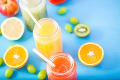 新近地被紧压的果汁,在明亮的蓝色ba的圆滑的人橙黄青绿的香蕉柠檬苹果橙色猕猴桃葡萄草莓 库存图片