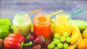 新近地被紧压的果汁,在木的黑暗的圆滑的人橙黄青绿的香蕉柠檬苹果橙色猕猴桃葡萄草莓 免版税图库摄影