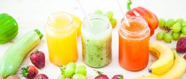 新近地被紧压的果汁,在木的黑暗的圆滑的人橙黄青绿的香蕉柠檬苹果橙色猕猴桃葡萄草莓 库存照片