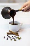 新近地酿造的浓咖啡调味用桂香和豆蔻果实 库存照片