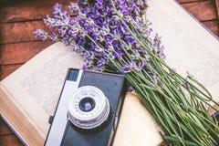 新近地cutted淡紫色花和葡萄酒照片照相机在一本开放书 木背景 免版税库存图片