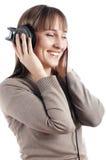 新迷人的微笑的女孩听到音乐我 免版税库存照片
