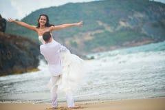 新郎举了新娘,手拉手传播 在爱的夫妇在海的一个离开的海滩 免版税库存照片