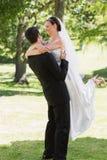 新郎举的新娘在庭院里 免版税库存图片