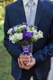 新郎举行婚礼花束在手中 库存照片