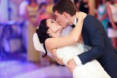 新郎亲吻弯曲她的一个新娘在他们的第一个舞蹈期间 免版税库存照片