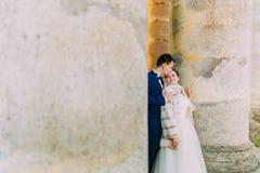 新郎亲吻面颊的新娘,当站立在古老大厦之间时的专栏 免版税库存照片