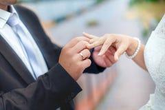 新郎佩带新娘在他的手指的一个婚戒 夫妇聘 免版税图库摄影