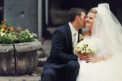 新郎告诉新娘秘密-新婚佳偶在一块老石头后安装 库存图片