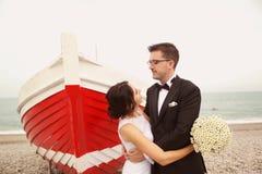 新郎和新娘在一条红色小船附近 免版税库存图片