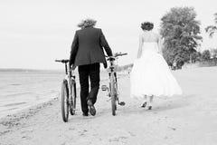 新郎和新娘在与自行车的海滩走 免版税库存图片