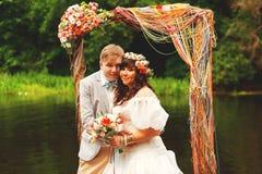 新郎和新娘在曲拱下在池塘附近 免版税库存图片