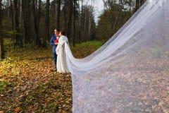 新郎和新娘有非常长的新娘面纱的 免版税图库摄影
