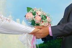 新郎和新娘的手有婚礼花束的 库存照片