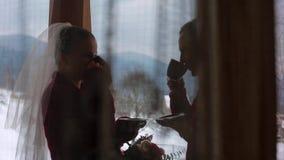 新郎和新娘饮料咖啡或茶在杯子外面在木日志瑞士山中的牧人小屋村庄在村庄和亲吻阳台与雪 影视素材