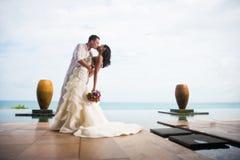 新郎在一个美丽的热带海滩,一对浪漫夫妇的一个清楚的晴天亲吻新娘 免版税库存图片
