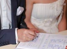 新郎在婚姻文件,选择聚焦投入她的署名 免版税库存照片