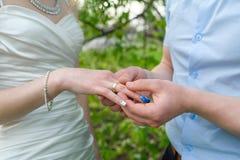 新郎在庭院里佩带新娘在他的手指的一只金戒指 库存照片