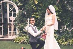 新郎在庭院里戴着新娘` s圆环 免版税库存照片