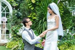 新郎在庭院里戴着新娘` s圆环 库存图片