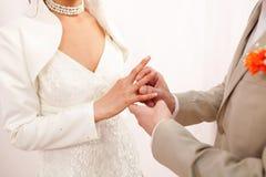 新郎在新娘上把婚戒放 免版税库存图片