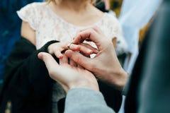 新郎在新娘的手指上把圆环放 秋天户外婚礼 附庸风雅 免版税图库摄影